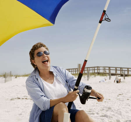 Mature woman seated on the beach fishing, at the moment she's got a bite! Stock Photo - 3050527