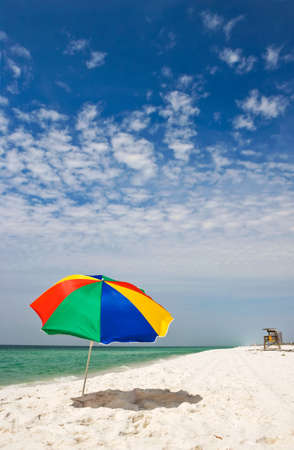 Sunny beach and colorful umbrella by emerald coastline. Good background or tropical mood photo.