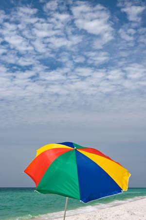 gusty: Bright beach umbrella on clean empty beach with emerald seacoast. Good background photo