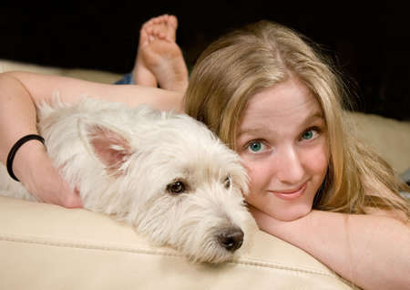 woman on couch: Portrait of a cute young woman enjoying quality time with her white West Highland Terrier Stock Photo
