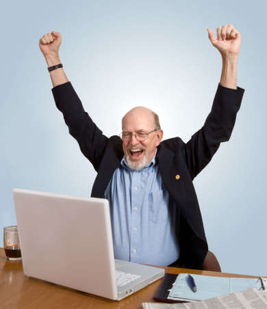 Senior man seated at desk, looking at computer, cheering over good news he has just received. photo