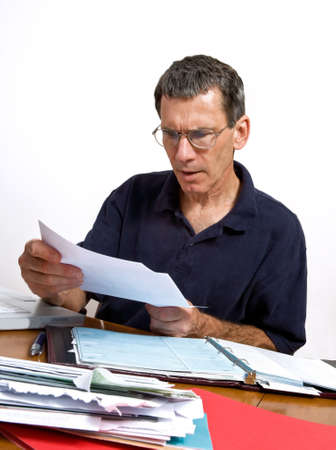 Man paying his monthly bills, looking shocked at a bill he just opened. Stock Photo - 3467604