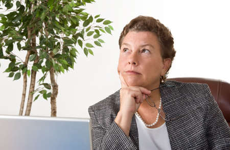 Mature businesswoman sitting at laptp in her office, pondering a decision. photo