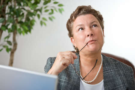 Mature businesswoman at her laptop, gazing into space and thinking. photo
