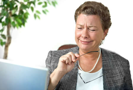 dismay: Attractive mature businesswoman looking with dismay, disbelief or amusement at her computer Stock Photo