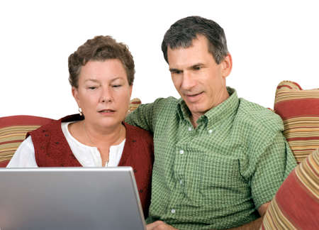 Mature couple sitting close working on the laptop computer photo