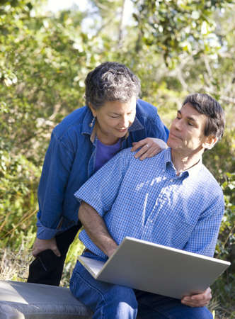 Happy mature couple having a laptop computer adventure. photo