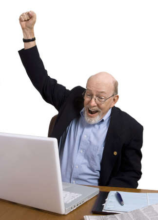 Senior man cheering with happiness at something hes just read on his laptop. photo
