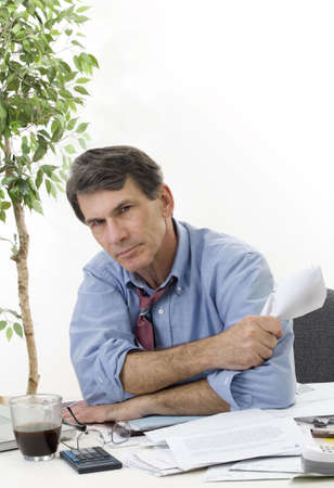 Fed-up, frustrated, stressed businessman at his desk, working late, trying to cover his expenses. Stock Photo - 4123250