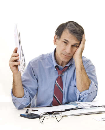 Stressed, tired, overworked businessman doing paperwork, worrying about the economy, his credit, etc. Stock Photo