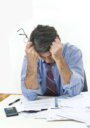 Middle aged man at his desk, holding his head, trying to make ends meet.