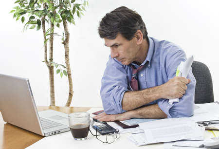 Stressed businessman at his office laptop, trying to find the best direction for his company. Stock Photo - 4142874