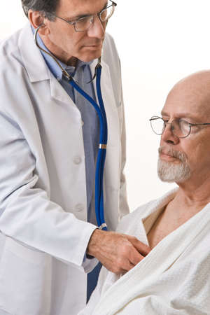 Closeup of male doctor listening to a senior male's heart and lungs with a stethoscope, white background.