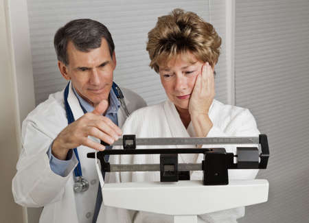 menopause: Woman looking dismayed at her weight as she is weighed by her doctor on a medical scale.