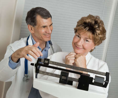 physical test: Medico con sorridente donna che ha raggiunto il suo obiettivo di peso dal punto di vista medico in scala medico. Archivio Fotografico