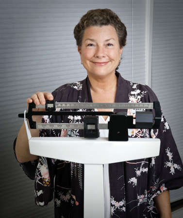 Smiling, happy, mature woman on a medical scale, pleased with the results of her weight-loss program.