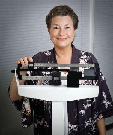 weight loss plan: Sorridente, felice, donna matura su una scala di medici, con soddisfazione i risultati del suo programma di perdita di peso.