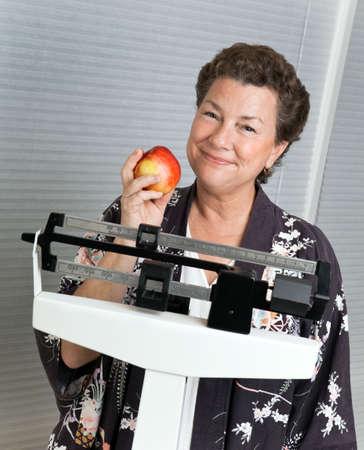 weight loss plan: Piuttosto maturo, la donna su una scala con un medico che illustrano ragionevole mela, una dieta sana.
