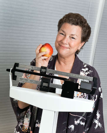 illustrating: Pretty mature, woman on a medical scale with an apple illustrating sensible, healthy dieting.