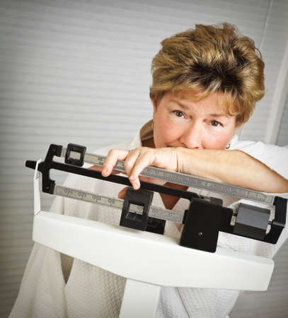 dieting: Closeup of a pretty but worried mature woman weighing herself on a medical scale.