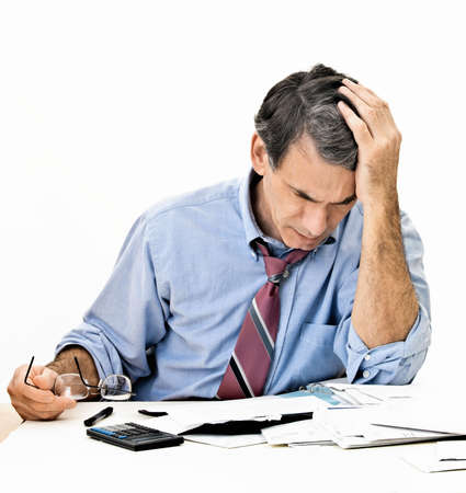 Man at Desk worrying about paying bills and bankruptcy photo