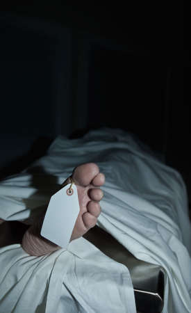 Dark atmospheric photo of body covered with a sheet in a morgue, feet toward camera with blank tag on the big toe. Foot clearly shows flaking skin and athlete's foot fungus as well as years of hard use. (body is a model)(body is a model)