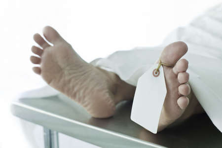 Photo of dead body covered with a sheet on a gurney, feet toward camera with blank tag on the big toe. Feet are smooth and clean. (body is a model)