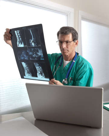 Doctor in scrubs at his laptop reviewing patient history and radiology scans.