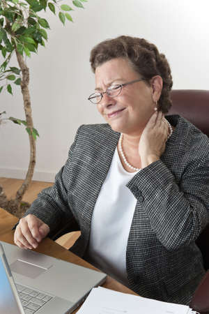 Mature executive businesswoman at her desk with a pain in the neck and headache, wincing and rubbing her neck