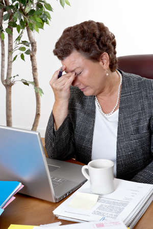 menopause: Mature business woman at her desk, eyes closed, worried about bills and financial problems