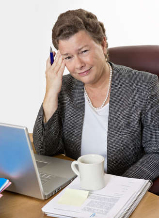 Mature businesswoman at her desk having a hot flash and a headache, looking at camera, very distressed.