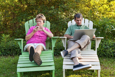 Couple outdoors relaxing...each busy with his own technology (laptop and MP3). Some motion blur. photo