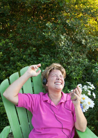 Attractive mature woman relaxing in an Adirondack chair in a lush outdoor setting, grooving on her mp3 tunes.