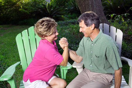 Laughing, happy couple arm wrestling in a green outdoor setting photo