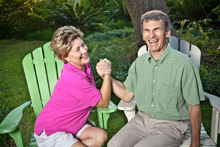 Happy mature couple arm wrestling outdoors. The woman is winning, the man is laughing. photo
