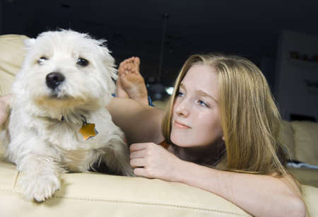 Cute young woman with her good friend, a White West Highland Terrier. Focus on the girl. photo