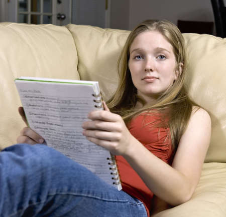 woman on couch: Girl studying for a test