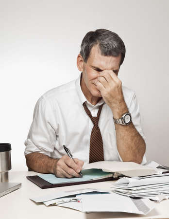 Worried, middle age man rubbing his forehead in pain, paying bills and writing checks Standard-Bild