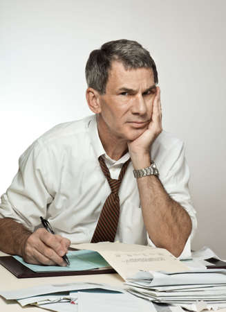 pay desk: Worried middle age man sitting at desk paying bills, writing checks, and looking stressed out. Stock Photo