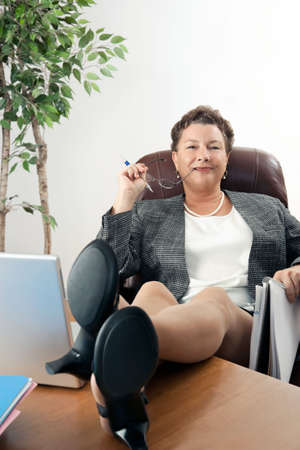 desk: Satisfied, confident mature businesswoman with feet up on desk.