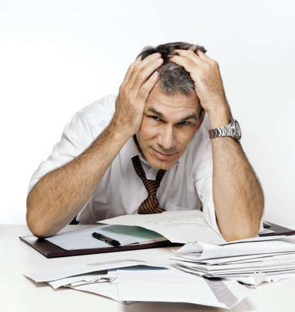 pay desk: Stressed man slumping over his desk covered with bills and overdue notices.