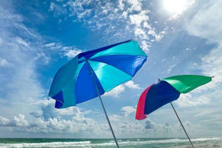 Multicolored beach umbrellas next to aqua ocean on a bright sunny windy day.