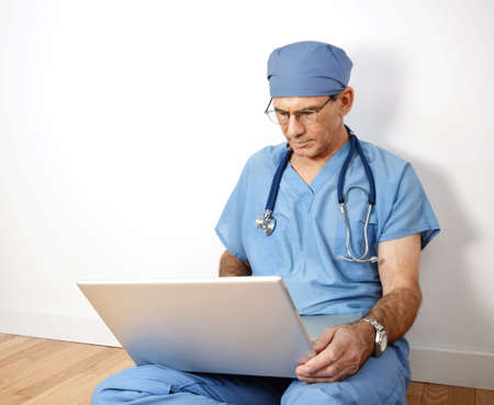 Mature doctor sitting on floor, leaning against wall, in blue scrubs, working on his laptop photo