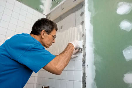 house renovation: Man applying ceramic tile to a bathtub enclosure wall.