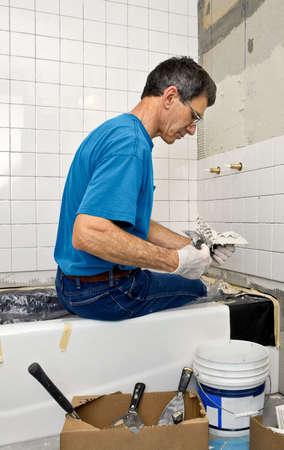 Man applying ceramic tile to a bathtub enclosure wall.