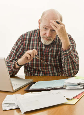 pay desk: Senior male worried about paying bills and bankruptcy Stock Photo