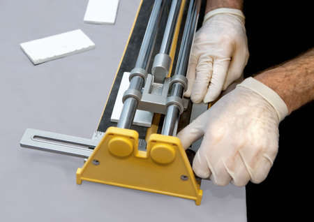 tile cutter: Closeup view of mans hands operating a tile cutter for cutting wall tiles.