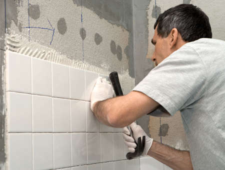 Man setting tile on cement board. He is tapping the tile in place with the handle of a hammer. Closeup. Real person on the job.