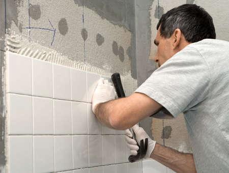 tapping: Uomo di impostazione delle mattonelle a bordo di cemento. Egli � toccando la piastrella in luogo con il manico di un martello. Closeup. Persona reale sul posto di lavoro.