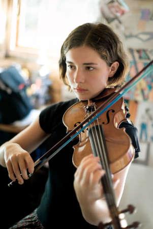 onderwijs: Mooie jonge vrouw beoefenen viool in een zonnige kamer. Beschikbaar licht, selectieve focus, focus scherpste op ogen.